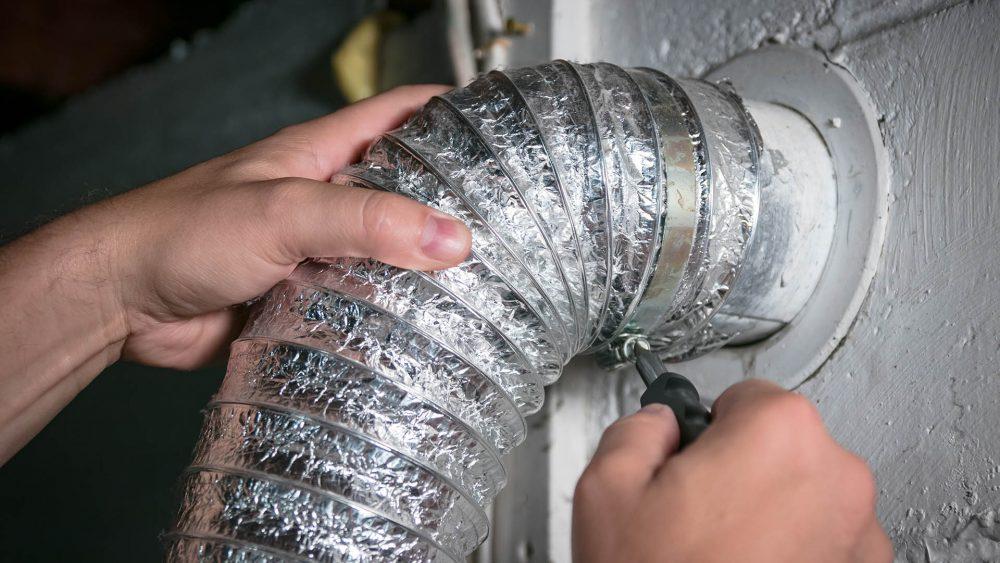 Eine Person schraubt einen Abluftschlauch an einem entsprechenden Anschluss im Haus fest.