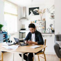 Eine Person sitzt an einem Tisch mit einem Laptop vor sich und arbeitet.