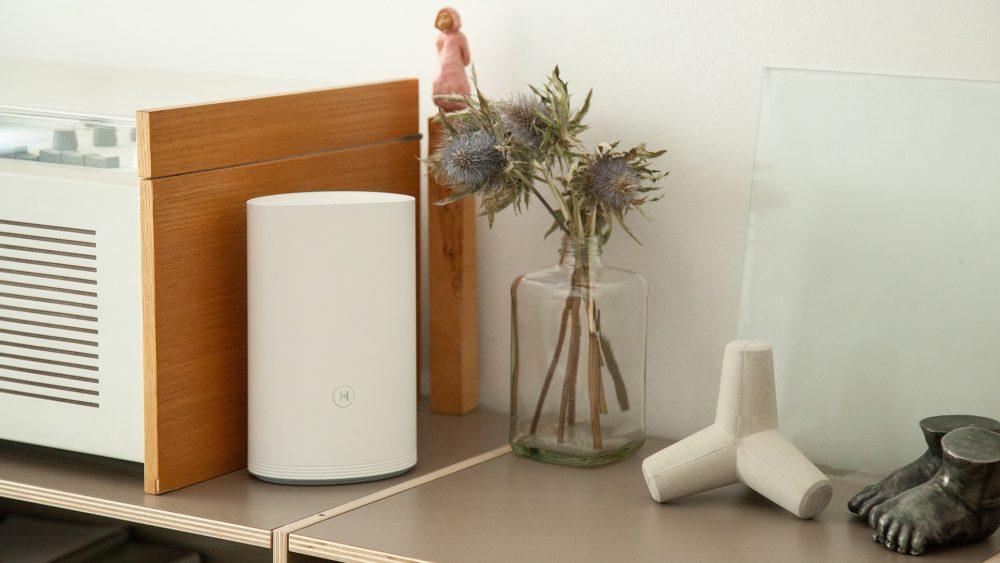 Ein Huawei-Router steht auf einem Regal zwischen diversen Deko-Artikeln.
