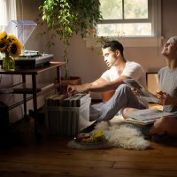 Zwei Personen sitzen auf dem Fußboden vor einer Plattenkiste und schauen sich die Schallplatten an.