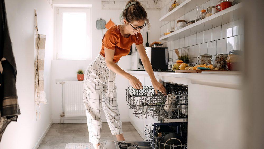Eine Person räumt eine Geschirrspülmaschine ein.