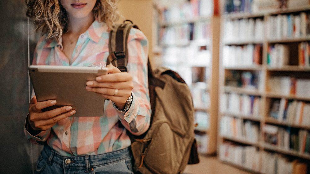 Eine Person steht in einer Bibliothek und hält ein iPad in den Händen.