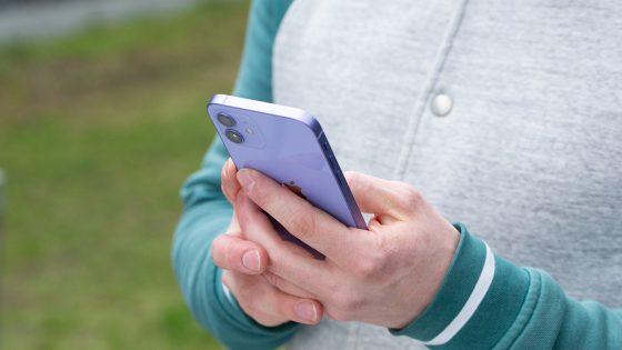 Eine Person hält ein iPhone in der Hand.